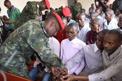 A military police officer takes hand-cuffs off suspects at the Military Tribunal in Nyamirambo, Kigali.