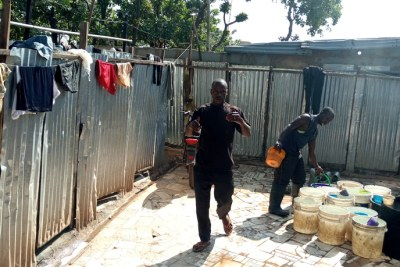 Baba Awolu is attends to a man who wants to use his local toilet and washroom facility