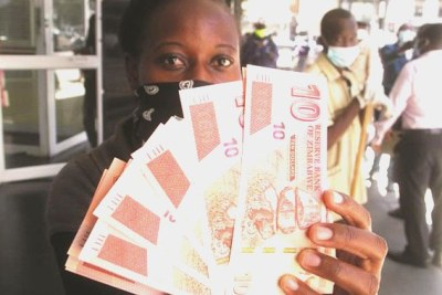 A woman displays the new $10 banknotes on her way out of a bank in Harare (file photo).