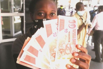 A woman displays the new $10 banknotes on her way out of a bank in Harare.