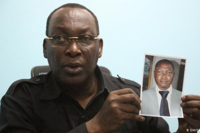 Chadema party leader Freeman Mbowe holds a picture of party member Daniel John who was mudered in 2018.