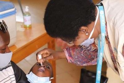 Dans un centre de santé de Ouagadougou, la capitale du Burkina Faso, Dre Marie Marcos, Spécialiste santé à l'UNICEF Burkina Faso, aide les infirmières à vacciner les enfants.