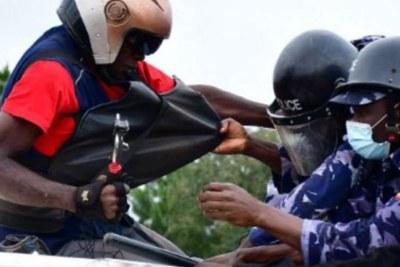 La police arrêtant le journaliste de Radio One Saif-llah Ashraf Kasirye (à gauche) dans le district de Luuka, en Ouganda, le 18 novembre.