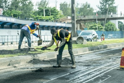 Workers on a section of Ikorodu Road in Lagos (file photo).