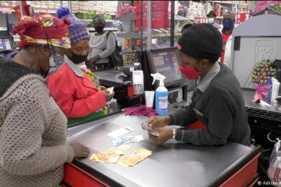 Two women in South Africa receive their social benefit handout at a supermarket checkout.